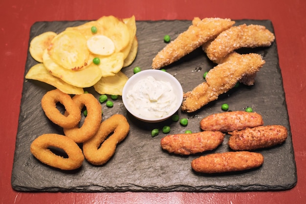 Fast-food-zwiebelringe, kartoffeln und gebratene hühnersoße auf einer dunklen tischansicht