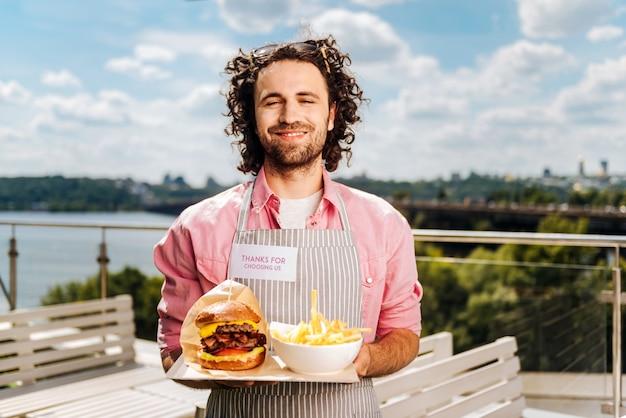 Fastfood. erfahrener lockiger, gutaussehender fast-food-arbeiter, der seinen kunden burger mit pommes bringt