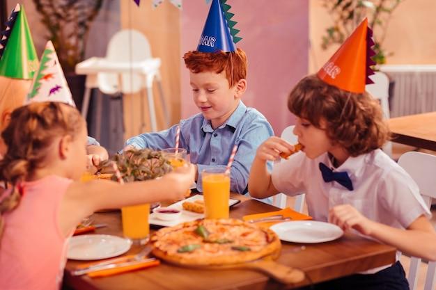 Fastfood. hübsches kind, das papierhut hat, während auf geburtstagsfeier ist