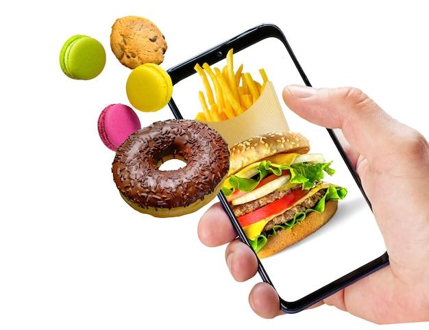 Fastfood online bestellen. hand hält telefon mit fast food, das aus dem bildschirm fliegt
