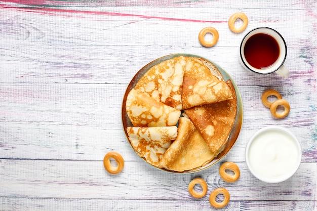 Fastnacht maslenitsa festival mahlzeit. russischer pfannkuchen-blini mit himbeermarmelade, honig, frischer sahne und rotem kaviar, zuckerwürfeln, hüttenkäse, bubliks auf hellem hintergrund
