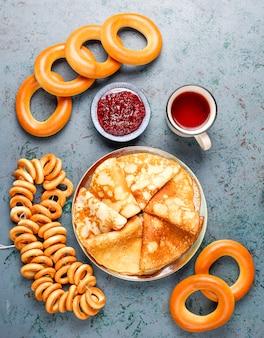 Fastnacht maslenitsa festival mahlzeit. russischer pfannkuchen-blini mit himbeermarmelade, honig, frischer sahne und rotem kaviar, zuckerwürfeln, hüttenkäse im dunkeln