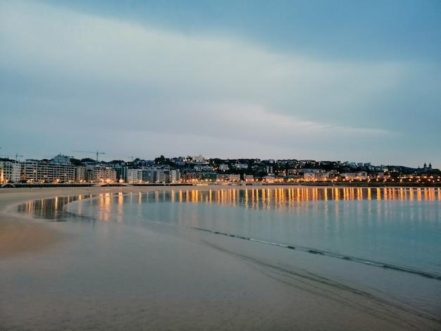 Faszinierende abendlandschaft der stadtlichter, die im ozean in san sebastian, spanien reflektieren