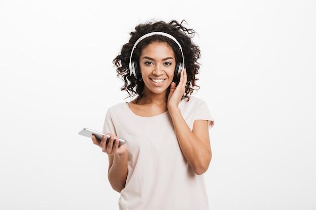 Faszinierende amerikanische frau mit lockiger frisur und großem lächeln, das musik über drahtlose kopfhörer hört, die silbernes smartphone in der hand halten, lokalisiert über weißer wand