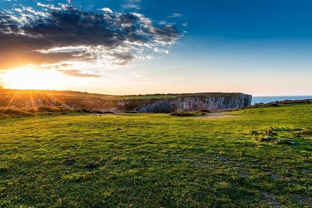 Faszinierende ansicht der felder nahe dem ozean während des sonnenaufgangs