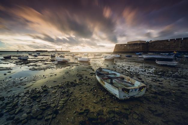 Faszinierende ansicht der seelandschaft mit den geparkten kleinen booten unter einem malerischen bewölkten himmel