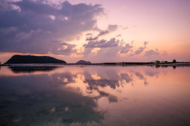 Faszinierende ansicht des himmels, der während des sonnenuntergangs im wasser reflektiert
