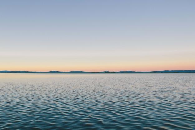 Faszinierende ansicht des ruhigen ozeans unter dem blauen himmel - perfekt für hintergrund