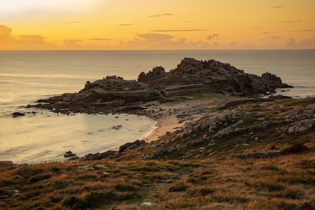 Faszinierende ansicht des ufers des ruhigen ozeans während des sonnenuntergangs in galizien, spanien