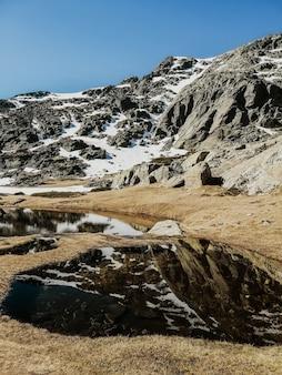 Faszinierende ansicht des wassers, das die umgebung im penalara-berg in spanien widerspiegelt