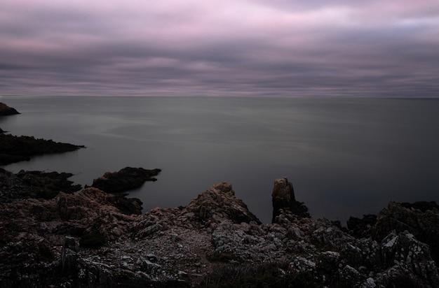 Faszinierende ansicht eines ruhigen ozeans an einem düsteren tag