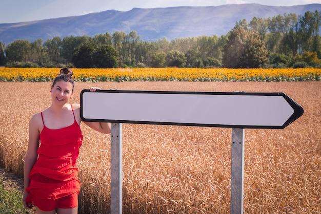 Faszinierende aufnahme einer attraktiven frau in einem roten kleid, die in einem weizenfeld mit straßenschild posiert
