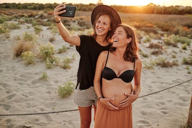 Faszinierende aufnahme eines schönen schwangeren paares - lesbisches familienkonzept