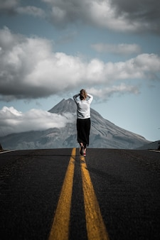 Faszinierende aussicht auf einen jungen touristen, der auf der leeren straße zum berg geht