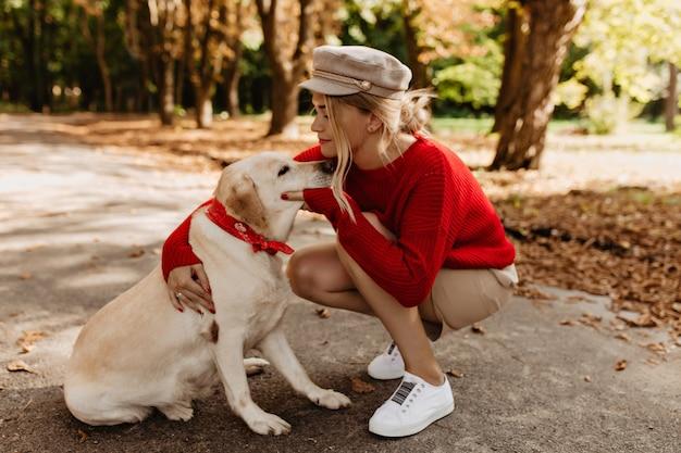 Faszinierende blondine mit entzückendem labrador, der tag zusammen im herbstpark verbringt. berührendes foto des mädchens in der saisonalen kleidung, die ihren geliebten hund umarmt.