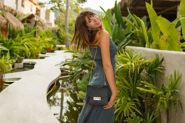 Faszinierende europäische frau im sommerkleid, das im tropischen ferienort geht. grüne tropische pflanzen auf hintergrund.