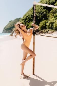 Faszinierende europäische weibliche modell tanzen in der nähe von volleyball in sommertag gesetzt. outdoor-schuss in voller länge des verspielten mädchens im orangefarbenen badeanzug, der spaß am strand mit dschungel hat.