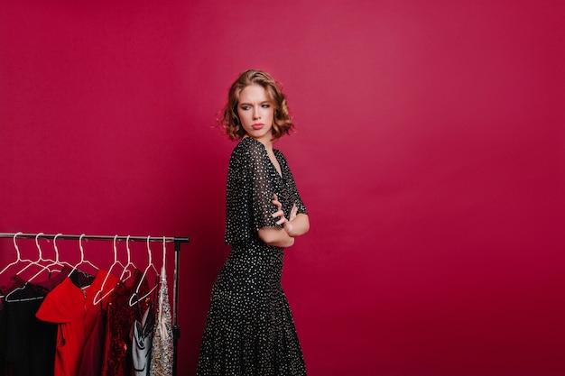 Faszinierende frau, die traurige gefühle in der boutique mit teuren kleidern ausdrückt