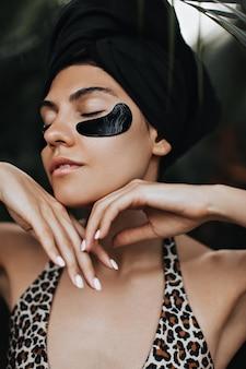 Faszinierende frau mit augenklappen, die auf naturhintergrund aufwerfen. atemberaubende junge dame im schwarzen turban, die gesichtsbehandlung genießt.