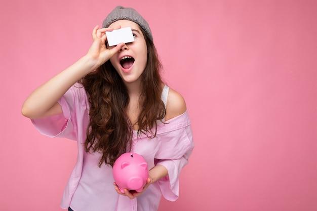 Faszinierende glückliche, fröhliche junge brünette frau mit hemd isoliert auf rosa hintergrund mit freiem