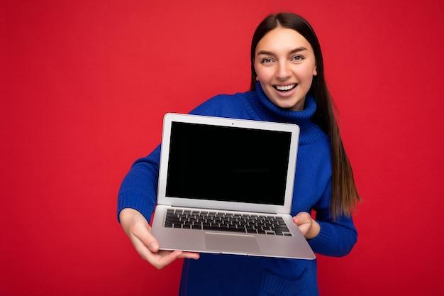 Faszinierende hübsche glückliche schöne junge brunet-frau, die computer-laptop mit blick auf die kamera mit blauem pullover über rotem wandhintergrund isoliert hält. freier platz für werbung