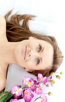 Faszinierende junge frau, die auf einer massagetabelle mit blumen liegt