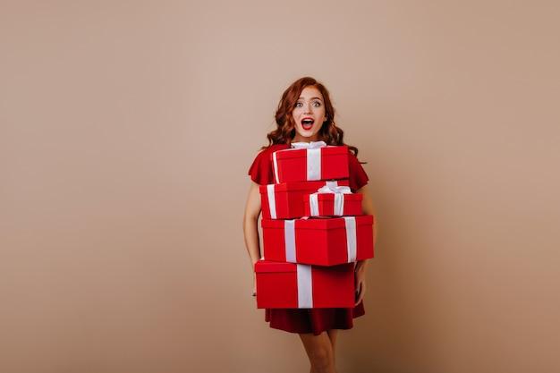 Faszinierende junge ginerfrau, die weihnachtsgeschenke hält. innenfoto des atemberaubenden mädchens, das mit überraschtem lächeln im neuen jahr aufwirft.