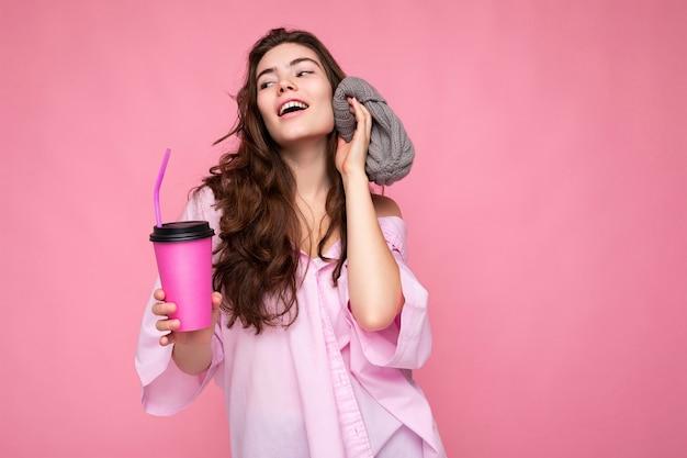 Faszinierende junge, positive, brünette, lockige frau mit rosafarbenem hemd und grauem hut einzeln auf rosafarbenem hintergrund, die eine papierkaffeetasse für mockup-trinken hält und spaß hat, zur seite zu schauen.