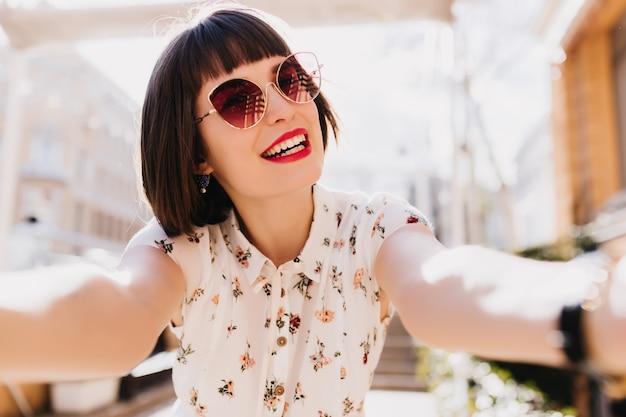Faszinierende kaukasische frau mit dunkelbraunem haar, das selfie am sonnigen morgen macht. außenporträt des romantischen mädchens in der trendigen bluse.