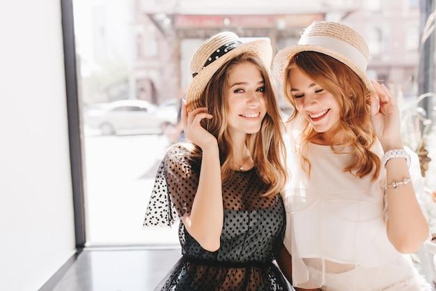 Faszinierende lächelnde mädchen im romantischen sommeroutfit scherzen, während sie das wochenende zusammen verbringen