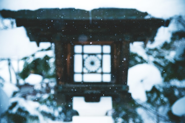 Faszinierende landschaft des schnees, der über eine tempellaterne in japan fällt