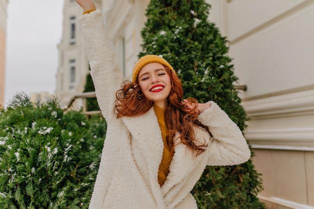 Faszinierende langhaarige frau, die nahe grüner fichte tanzt. foto im freien des lachenden ingwermädchens im stilvollen mantel.