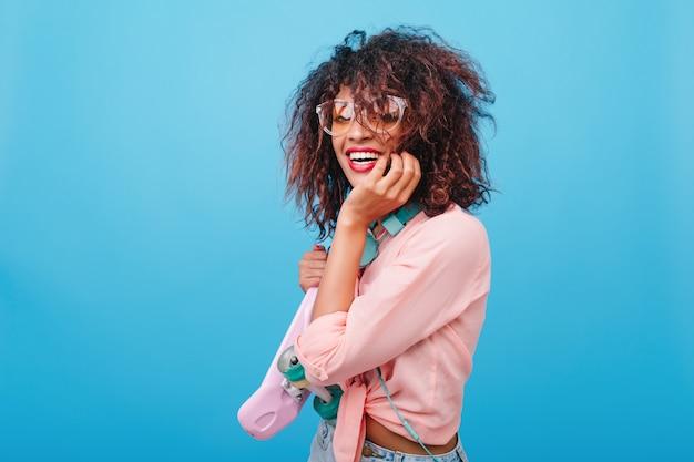 Faszinierende süße frau mit brauner haut, die nachdenklich posiert und gesicht mit hand stützt. attraktive mulattenfrau im weinlese rosa outfit lächelnd