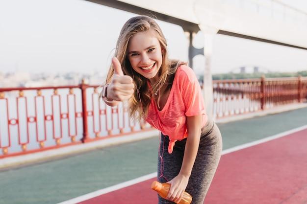 Faszinierende weibliche läuferin, die mit dem daumen nach oben aufwirft. porträt des liebenswerten kaukasischen mädchens, das morgentraining genießt.