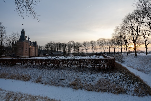 Faszinierender sonnenaufgang über dem historischen doorwerth schloss während des winters in holland