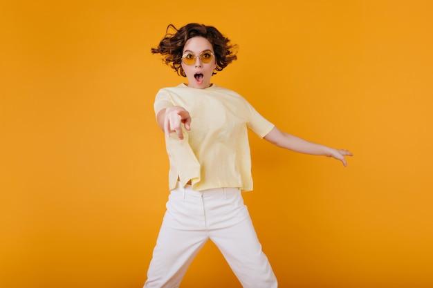 Faszinierendes blasses mädchen, das mit geschocktem gesichtsausdruck und offenem mund aufwirft. spektakuläre junge dame in der orangefarbenen sonnenbrille und im gelben t-shirt, die erstaunen ausdrücken.