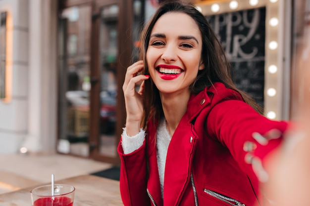 Faszinierendes braunhaariges mädchen, das selfie macht, während es im straßencafé ruht