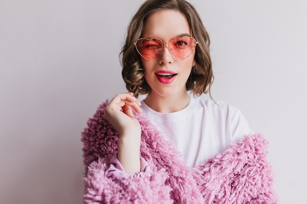 Faszinierendes brünettes mädchen im rosa pelzmantel, der spielerisch auf weißer wand aufwirft. liebenswerte anmutige frau in flauschiger jacke.