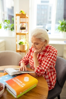 Faszinierendes buch. gut aussehende ältere frau, die beim lesen eines buches auf die seiten schaut