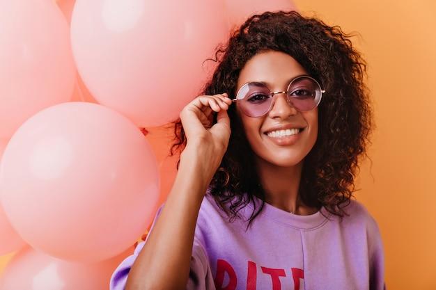 Faszinierendes geburtstagskind, das ihre brille während des schusses berührt. modische afrikanische frau, die rosa partyballons hält.