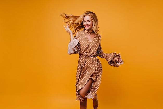 Faszinierendes kaukasisches modell im kleidertanzen mit lächeln. wunderschönes blondes mädchen lokalisiert auf gelber wand.