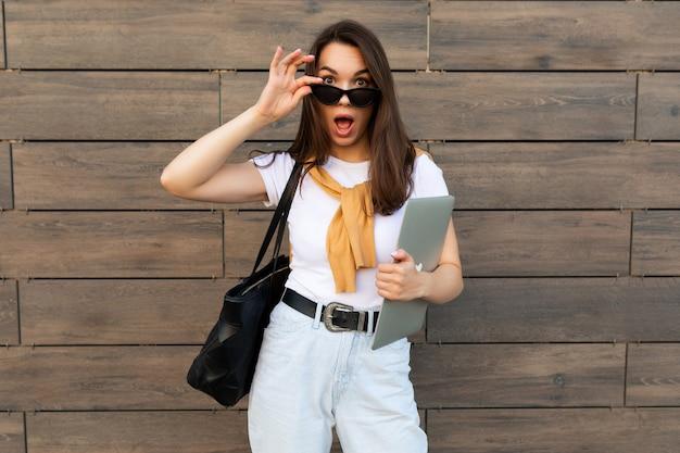 Faszinierendes, schönes, lächelndes, charmantes junges brunet-mädchen, das die kamera mit computer-laptop und schwarzer sonnenbrille in weißem t-shirt, gelbem pullover und hellblauer jeans auf der straße anschaut