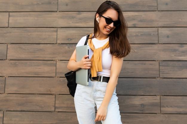 Faszinierendes schönes lächelndes charmantes junges brunet-mädchen, das mit computer-laptop und schwarzer sonnenbrille nach unten schaut