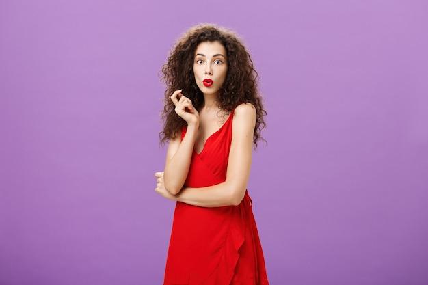 Faszinierte chamälere elegante dame mit lockiger frisur in rotem kleid und lippenstift, die neugierig die lippen faltet...