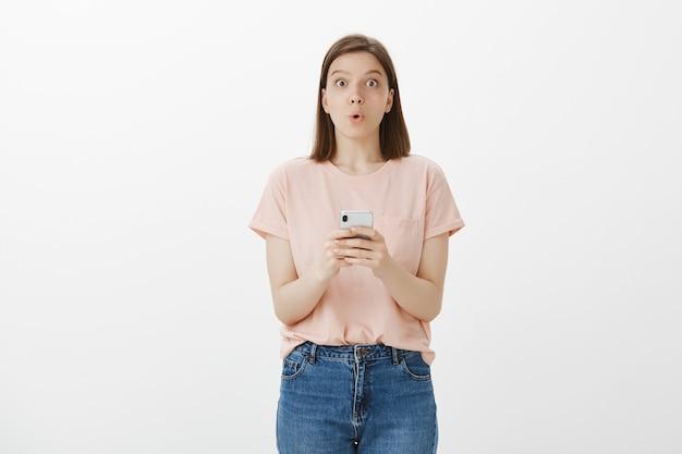 Faszinierte junge frau, die lippen faltet, erstaunt nach dem lesen der nachricht auf smartphone, unter verwendung der handy-app