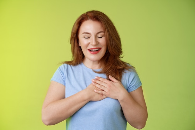 Faszinierte niedliche rothaarige leidenschaftliche frau mittleren alters seufzt reizende berührung herz schließen augen lächelnd entzückt ausdruck bewunderung versuchung gefühl wertschätzung dankbare emotionen grüne wand
