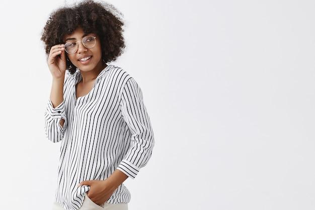 Faszinierte sinnliche und attraktive dunkelhäutige mitarbeiterin mit brille und gestreifter bluse, die sich mit einem koketten, amüsierten lächeln nach rechts dreht und die brille berührt und den süßen kerl überprüft
