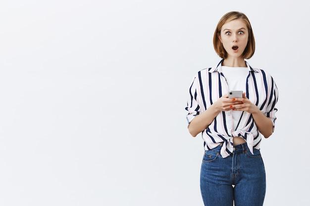 Faszinierte und aufgeregte junge frau, die nachrichten oder bankkonto am telefon prüft und nach smartphone-benachrichtigung erstaunt schaut