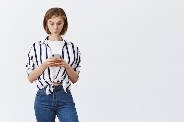 Faszinierte und aufgeregte junge frau, die nachrichten oder bankkonto am telefon prüft und smartphone erstaunt ansieht