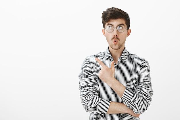 Faszinierter begeisterter attraktiver europäischer mann mit schnurrbart in brille, zeigt und schaut auf die obere linke ecke, sagt wow mit gefalteten lippen, ist zufrieden und neugierig mit dem kopierraum